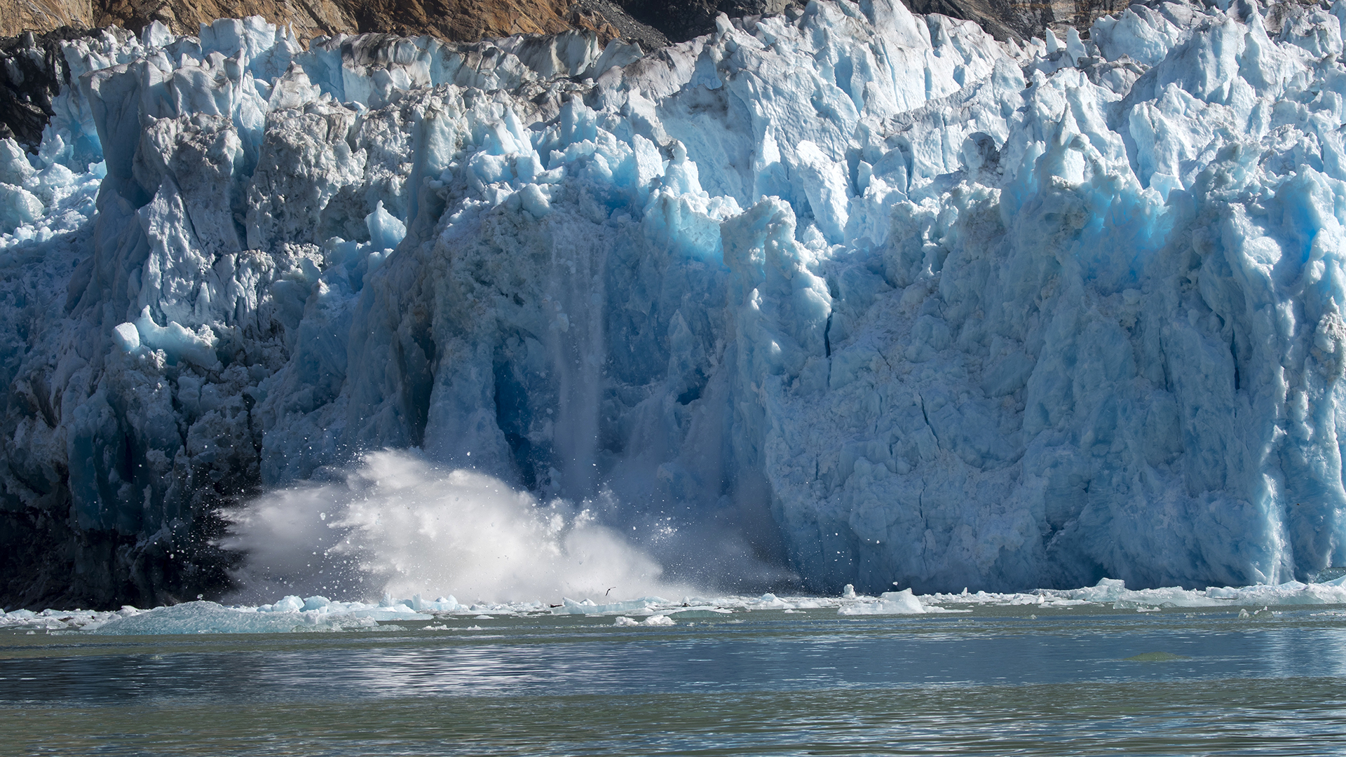 Chunks of ice are calving from the glacier face of the South